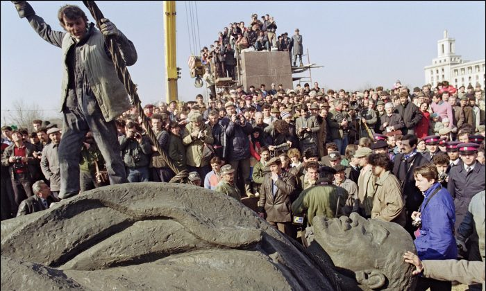 A Romanian worker stands atop the statue, sculptured in a pure style of socialist realism, of Russian Bolshevik revolutionary leader Vladimir Ilyich Lenin after it was removed from its pedestal on March 5, 1990, in Bucharest. Romanian communist dictator Nicolae Ceausescu and his wife Elena were executed by firing squad on Dec. 25, 1989, in Bucharest after being found guilty by an army tribunal of 'crimes against the people'. (Andre Durand/AFP/Getty Images)
