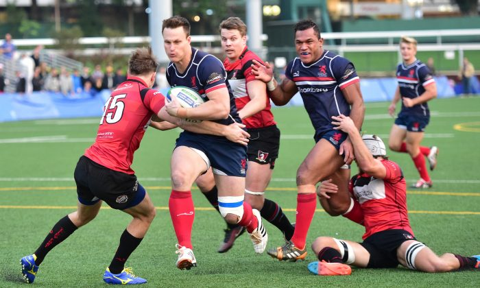 Bryan Rennie brushes past the Societe Generale Valley defence to score a try for Bloomberg HK Scottish in their Premiership match at Valley-8 on Saturday Dec. 13, 2014. (Bill Cox/Epoch Times)