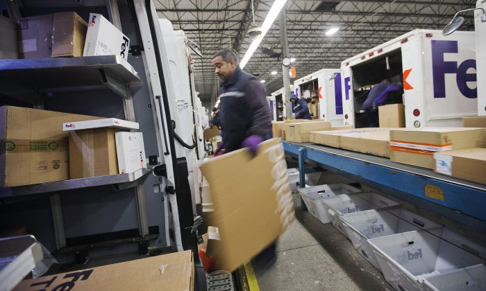 In this Dec. 15, 2014 photo, courier Stephen Werts loads packages onto a truck for delivery at a FedEx facility, in Marietta, Ga. FedEx reports quarterly financial results on Wednesday, Dec. 17, 2014. (AP Photo/David Goldman)