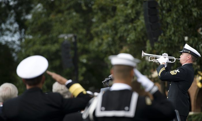 Two sailors salute as taps is played during a memorial service at the Marine barracks in Washington D.C., Sept. 22, 2013. (Courtesy Erin A. Kirk-Cuomo/Department of Defense)
