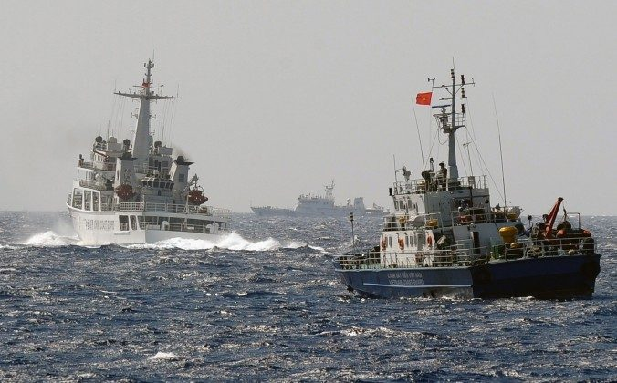 A China Coast Guard ship (L) blocks the way of a Vietnam Coast Guard ship on May 14, near to the site of a Chinese drilling oil rig (R, background) being installed at the disputed water in the South China Sea off Vietnam's central coast. (Hoang Dinh Nam/AFP/Getty Images)
