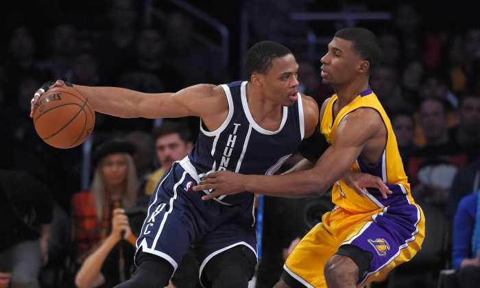 Oklahoma City Thunder guard Russell Westbrook, left, tries to drive by Los Angeles Lakers guard Ronnie Price during the first half of an NBA basketball game, Friday, Dec. 19, 2014, in Los Angeles. (AP Photo/Mark J. Terrill)