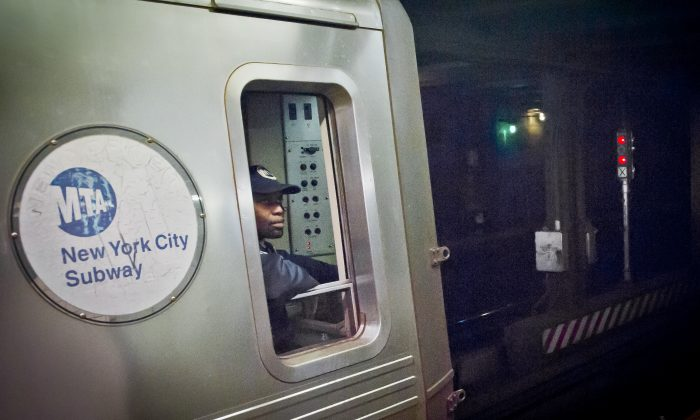 A Metropolitan Transit Authority (MTA) subway train operator waits for red-light signal, controlled by a manual subway interlocking switch and signal system, to go green, in New York, on Dec. 16, 2014. Transit officials are now replacing the 1930s manual signal system with 21st century digital technology that will allow more trains to travel closer together and a growing ridership to move around the city faster. (AP Photo/Bebeto Matthews)