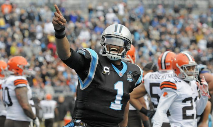 Carolina Panthers' Cam Newton (1) celebrates after running for a touchdown against the Cleveland Browns in the first half of an NFL football game in Charlotte, N.C., Sunday, Dec. 21, 2014. (AP Photo/Mike McCarn)