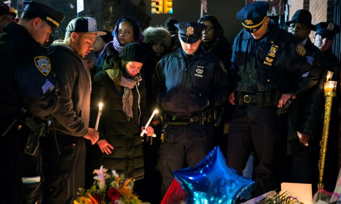 Police officers and other mourners stand in silence, Sunday, Dec. 21, during a candlelight vigil near the spot where two New York Police Department officers, sitting inside a patrol car the previous day, were shot by an armed man, killing them both. The assailant then went into a nearby subway station and committed suicide, police said. (AP Photo/Craig Ruttle)
