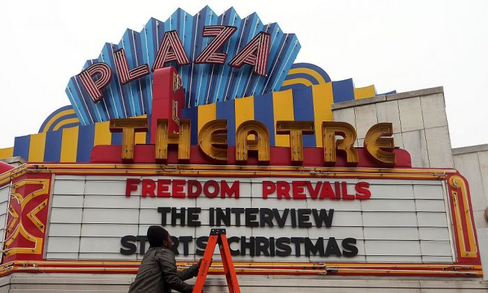 "A man finishes hanging the marquis for ""The Interview,"" at the Plaza Theatre in Atlanta, on Tuesday in which the theater will show on Christmas day. (AP Photo/Atlanta Journal-Constitution, Ben Gray)"
