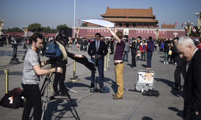 Foreign journalists work in Tiananmen Square on Nov. 9 in Beijing. (Fred Dufour/AFP/Getty Images)