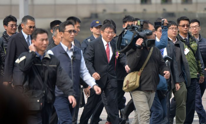 Taipei mayor Dr. Ko Wen-je (center, red tie) surrounded by reporters on his first day in office on Dec. 25, 2014. (CNA News)
