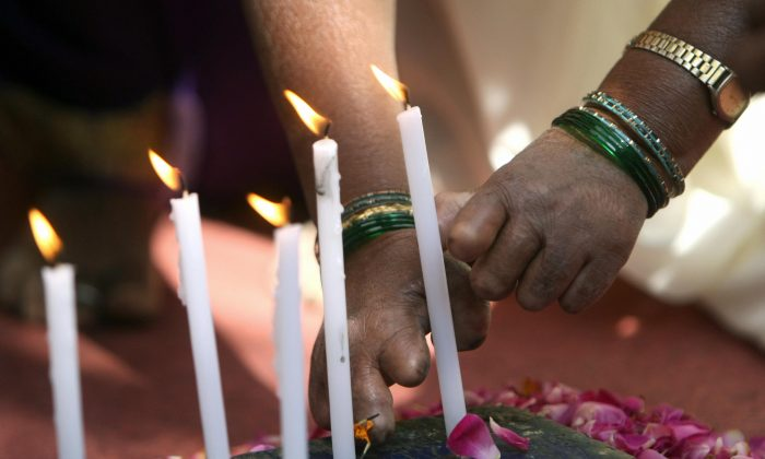 Indian leprosy patients light candles in remembrance of police officials who died in the Mumbai terror attacks, in Mumbai on Dec. 26, 2008. (Pal Pillai/AFP/Getty Images)