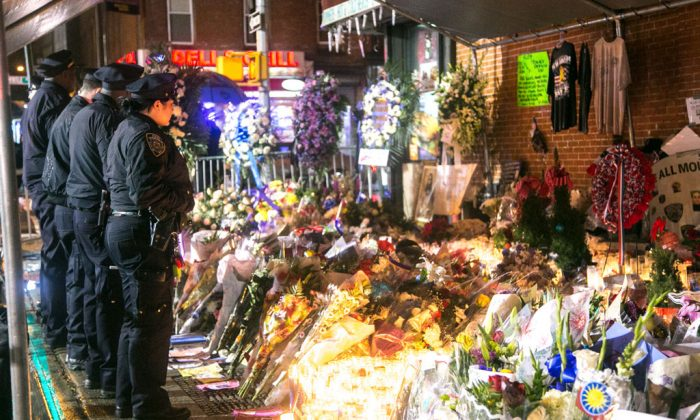 New York Police Department officers visit a makeshift memorial in Brooklyn, New York, on Dec. 24, for the officers who were murdered in their police car by an emotionally disturbed man. (Benjamin Chasteen/Epoch Times)