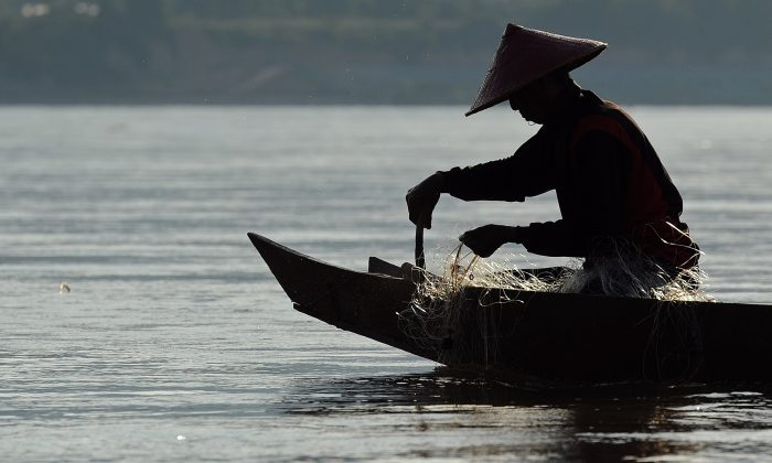 A fisherman pulls his net from the Mekong River in northern Thailand and bordering Laos on May 29, 2013. The waters of the mighty Mekong have sustained generations of families but nowadays its fishermen often find their nets empty and fear hydropower mega-dams will destroy their livelihoods. (Christophe Archambault/AFP/Getty Images)