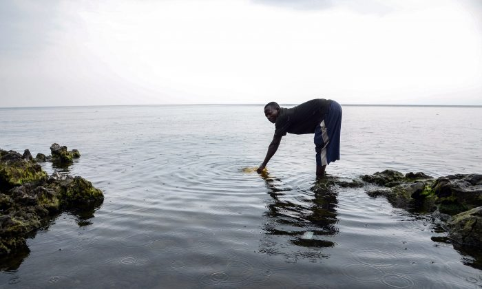 A man fills a container with water in Lake Kivu in the Democratic Republic of Congo on June 16, 2014. Lake Kivu is near the northeastern city of Goma, where most of the one million residents of the city are still waiting to have clean, uncontaminated running tap water in their homes. Goma lies on the edge of one of the largest soft water reservoirs in the world, lake Kivu, where it is rains abundantly, but most people have to go to the lake to fetch water, chlorinate it for drinking or buy some from sellers, who make about 10 US dollars a day, transporting an average of 120 liters (30 gallons) on bicycles from the lake to the city. (Junior D.Kannah/AFP/Getty Images)
