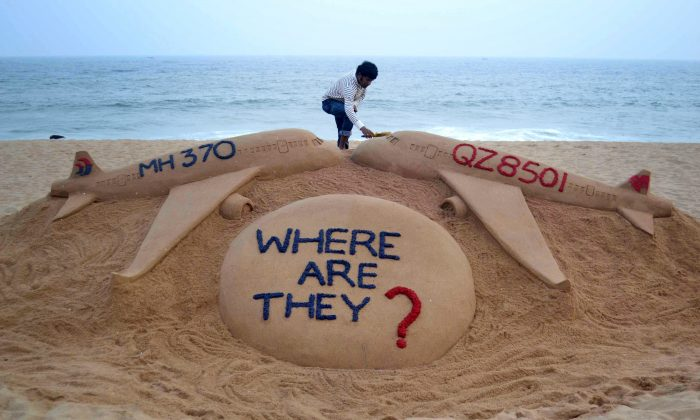 Indian sand artist Sudarsan Pattnaik gives the final touches to his sand sculpture portraying two missing aircraft, Air Asia QZ8501 and Malayasia Airlines MH370 on Golden Sea Beach at Puri, east of Bhubaneswar on Monday. (STRDEL/AFP/Getty Images)