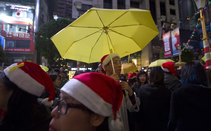 The guy in the Christmas hat and holding the yellow umbrella is clearly both merrymaker and protester... or neither?!? (AP Photo/Kin Cheung)