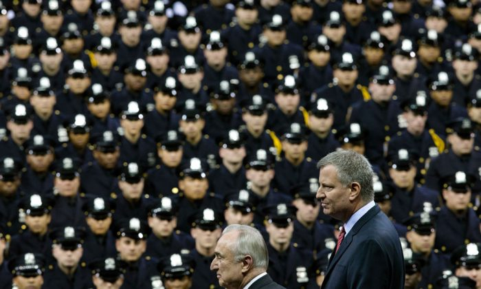NYC Mayor Bill de Blasio (R) and NYPD police commissioner Bill Bratton (C) stand on stage during a New York Police Academy graduation ceremony, Monday, Dec. 29, 2014, at Madison Square Garden in New York. Nearly 1000 officers were sworn in as tensions between city hall and the NYPD continued following the Dec. 20 shooting deaths of officers Rafael Ramos and Wenjian Liu. (AP Photo/John Minchillo)