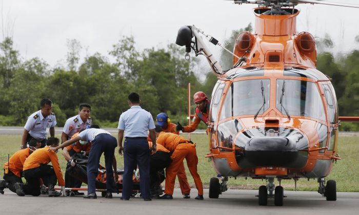 Officers of the National Search And Rescue Agency (BASARNAS) and Indonesian Air Force personnel unload a body of one of the victims on board AirAsia Flight 8501 from a helicopter at the airport in Pangkalan Bun, Indonesia, Wednesday, Dec. 31, 2014. The first proof of the jet's fate emerged Tuesday in an area not far from where it dropped off radar screens on Sunday morning. Searchers found  bodies and debris that included a life jacket, an emergency exit door and a suitcase about 10 miles from the plane's last known coordinates. (AP Photo/Achmad Ibrahim)