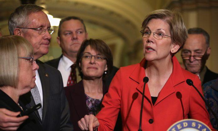 U.S. Sen. Elizabeth Warren (D-Mass.) (5th L) speaks to members of the media as (L-R) Sen. Patty Murray (D-Wash.), Senate Majority Leader Sen. Harry Reid (D-Nev.), Sen. Jon Tester (D-Mont.), Sen. Amy Klobuchar (D-Minn.), and Sen. Charles Schumer (D-N.Y.) listen after a Democratic Senate leadership election at the U.S. Capitol on Nov. 13, 2014. (Alex Wong/Getty Images)