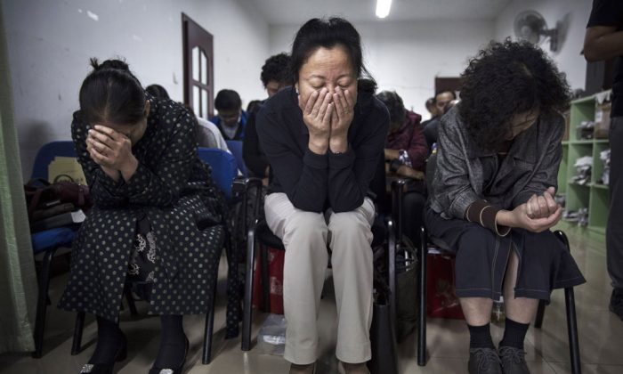 Chinese Christians pray during a service at an underground independent Protestant Church on Oct. 12, in Beijing, China. China, an officially atheist country, places a number of restrictions on Christians and allows legal practice of the faith only at state-approved churches. (Kevin Frayer/Getty Images)