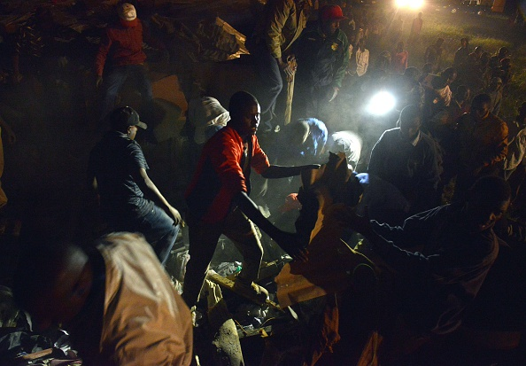 Civilian volunteers help carry away debris from the scene of a collapsed multi-storey residential building, January 04, 2014 in densely populated Huruma estate area of Kenyan capital, Nairobi. (TONY KARUMBA/AFP/Getty Images)