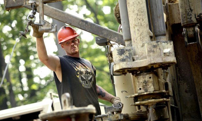 Linn Energy LLC relief driller Jim Williams loads drill rods onto a drill rig in Indiana, Pa. in 2006. (Andrew Rush/AP)