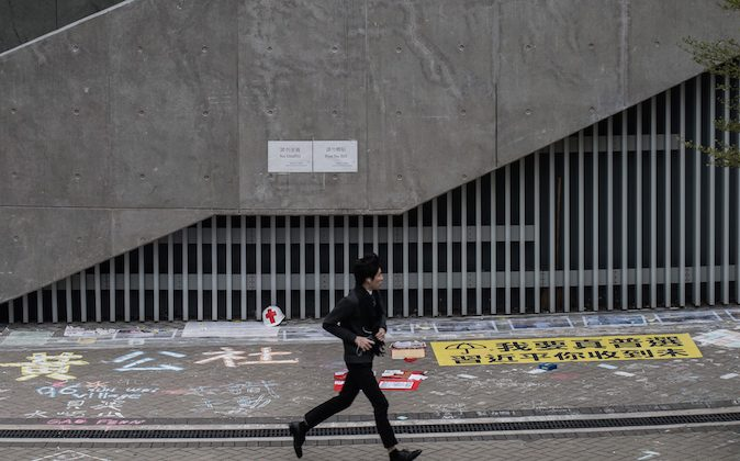 """A man runs past the """"Lennon Wall,"""" an area next to the Hong Kong central government offices where pro-democracy activists wrote messages of support for the protest movement, in Hong Kong on Jan. 5, 2015."""