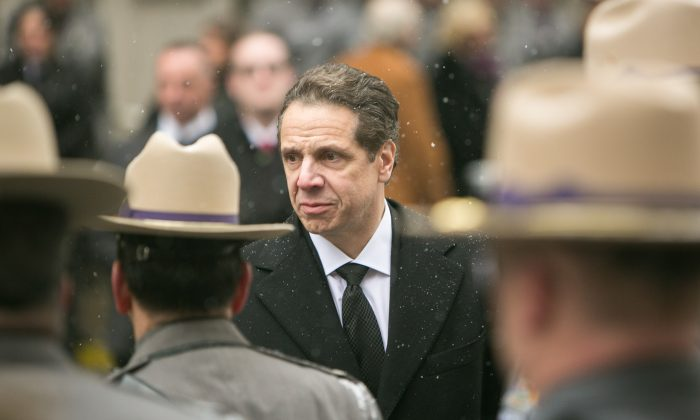 New York Governor Andrew Cuomo holds his mother's hand as they walk behind the casket of his father, Mario Cuomo, following the funeral service in Manhattan on Jan. 6, 2015. (Benjamin Chasteen/Epoch Times)