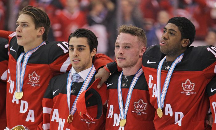 "Canadian junior hockey players (L-R) Jake Virtanen, Robby Fabbri, Max Domi, and Anthony Duclair stand for ""O Canada"" after winning the gold medal at the Air Canada Centre in Toronto on Jan. 5, 2015. (Claus Andersen/Getty Images)"