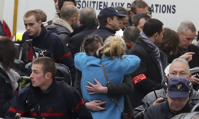 People hug each other outside the French satirical newspaper Charlie Hebdo's office, in Paris, Wednesday, Jan. 7, 2015. Masked gunmen stormed the offices of a French satirical newspaper Wednesday, killing 12 people before escaping, police and a witness said. (AP Photo/Remy de la Mauviniere)