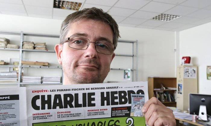 In this Sept.19, 2012 file photo, Stephane Charbonnier also known as Charb , the publishing director of the satirical weekly Charlie Hebdo, displays the front page of the newspaper as he poses for photographers in Paris. (AP Photo/Michel Euler, File)