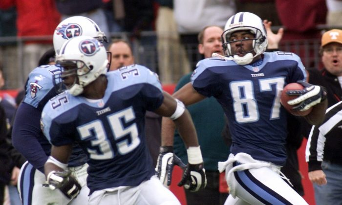Tennessee Titans wide receiver Kevin Dyson (87) looks back as he returns a kickoff with seconds remaining in the fourth quarter to defeat the Buffalo Bills in their AFC wild card game on Saturday, Jan. 8, 2000. The ball was lateralled twice on the return and Dyson took it to the endzone. Blocking for Dyson are Perry Phenix (35) and Greg Favors (51). (AP Photo/Wade Payne)