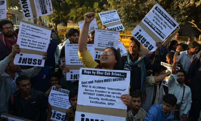 Indian residents on Dec. 7, 2014, hold placards and chant slogans as they take part in a protest against the alleged rape of a passenger by a driver working for the Uber taxi company in New Delhi. Following the incident, Uber and other app-based taxi services were banned in the city. (STRDEL/AFP/Getty Images)