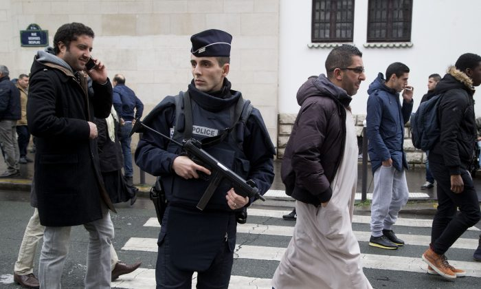 File - In this Friday, Jan. 9, 2015 file photo, a French police officer stands guard outside the Grand Mosque as people arrive for Friday prayers, in  Paris, France. Amid violence like the attack in Paris on a satirical newspaper over its depictions of the Prophet Muhammad, there's been increasing discussions among Muslims who say their community must re-examine their faith to modernize its interpretations and sideline extremists. There is a growing debate within Islam about whether and how to reject a radical minority that some fear is dragging them into conflict and wrecking the faith. (AP Photo/Michel Euler, File)