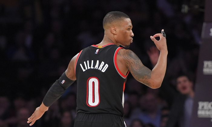 Portland Trail Blazers guard Damian Lillard gestures after scoring during the second half of an NBA basketball game against the Los Angeles Lakers, Sunday, Jan. 11, 2015, in Los Angeles. (AP Photo/Mark J. Terrill)
