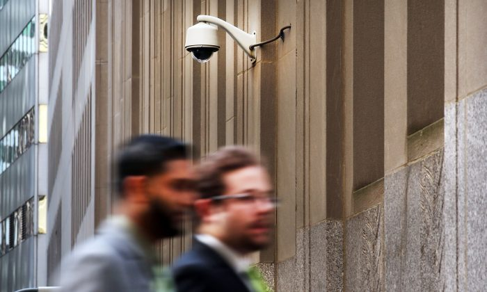 People walk by a surveillance camera along a street in the Financial District in New York on April 24, 2013. (Spencer Platt/Getty Images)