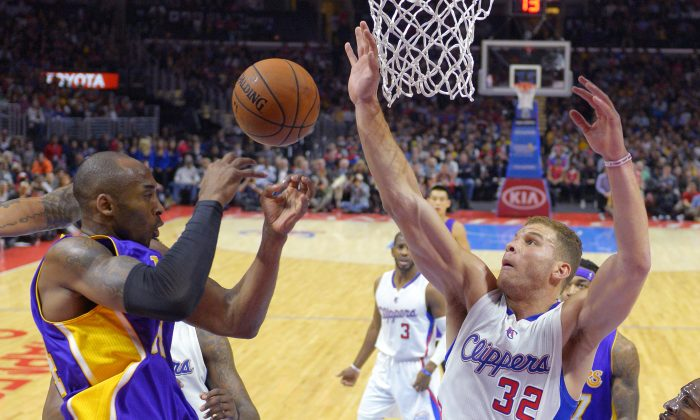Los Angeles Lakers guard Kobe Bryant, left, passes the ball as Los Angeles Clippers forward Blake Griffin defends during the first half of an NBA basketball game, Wednesday, Jan. 7, 2015, in Los Angeles. (AP Photo/Mark J. Terrill)