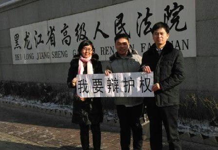 Lawyer Wang Yu (L), lawyer Zhang Weiyu (R), and Zhang's assistant Ren Feixiang (C) hold a banner that says