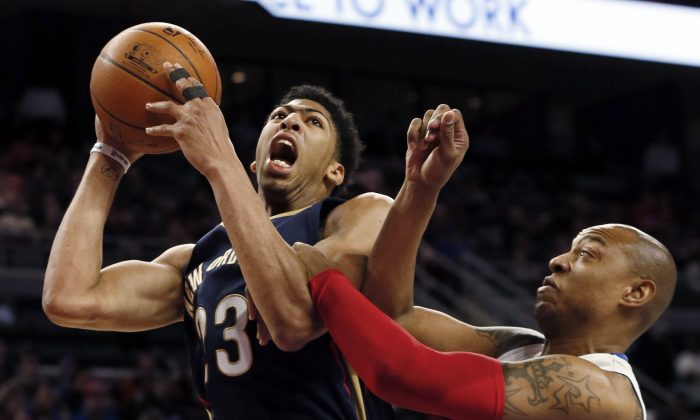 New Orleans Pelicans forward Anthony Davis (23) is fouled by Detroit Pistons forward Caron Butler during the second half of an NBA basketball game in Auburn Hills, Mich., Wednesday, Jan. 14, 2015. (AP Photo/Paul Sancya)
