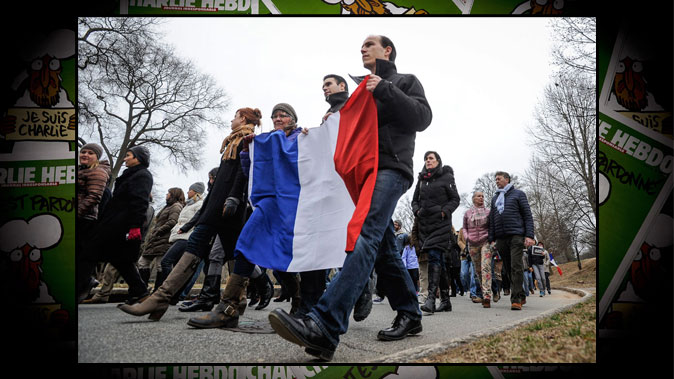 Front: French expatriates David Nalmin (R), Gabriel Giraldi, and American Patty Rasmussen carry a French flag through Piedmont Park in Atlanta, Sunday, to support France after terrorism around Paris that killed 17 people last week, on Jan. 11, 2015. (AP Photo/John Amis) Background: Copies of the latest edition of the magazine Charlie Hebdo on Jan. 14, 2015. (Joel Saget/AFP/Getty Images)