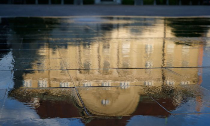 The Swiss central bank is reflected in a fountain in Bern, Switzerland, on May 18, 2014. (AP Photo/Keystone, Peter Klaunzer)