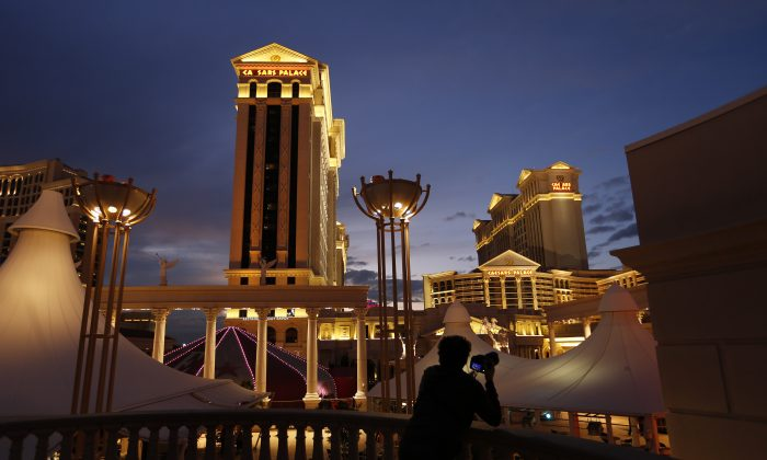 In this Monday, Jan. 12, 2015 file photo, a man takes pictures of Caesars Palace hotel and casino, in Las Vegas. A cash-strapped division of casino giant Caesars Entertainment Corp. said early Thursday Jan. 15, 2015 that it filed for bankruptcy protection in Chicago, hoping the court agrees to its plan to get out from under $18.4 billion of debt.  (AP Photo/John Locher, File)