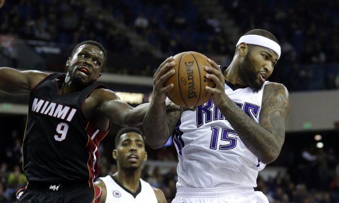 Sacramento Kings center DeMarcus Cousins,  right, pulls a rebound away from Miami Heat forward Luol Deng, left, of South Sudan, as Kings forward Jason Thompson looks on during the first quarter of an NBA basketball game in Sacramento, Calif., Friday, Jan. 16,  2015. (AP Photo/Rich Pedroncelli)