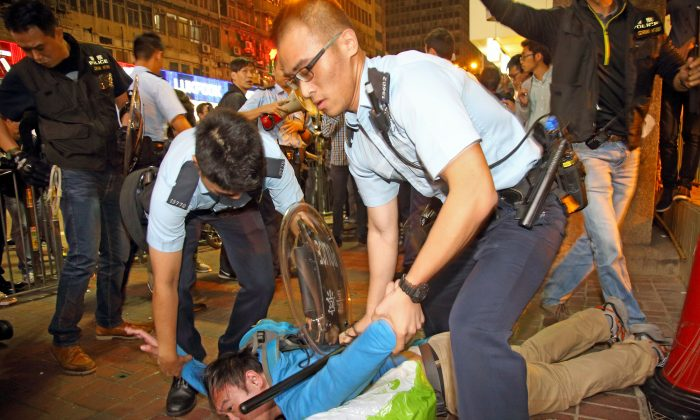 Police nab a pedestrian in Mong Kok, Hong Kong on Nov. 26, 2014. (Poon Cai Shu/Epoch Times)