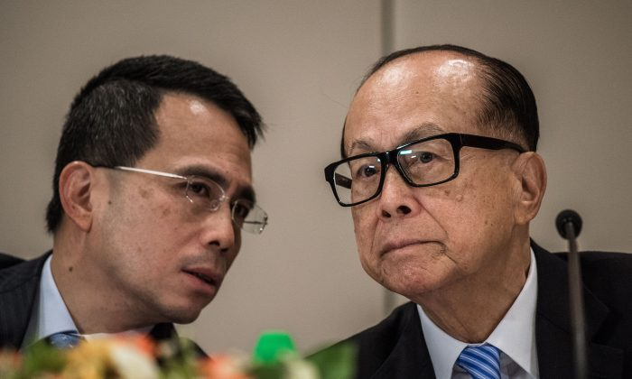 Hong Kong tycoon Li Ka-shing (R) listens to his son Victor Li Tzar-kuoi during a press conference in Hong Kong, on Jan. 9, 2015. According to democracy activist Edward Chin, Asia's richest man is feeling the pressure from Beijing. (Phillipe Lopez/AFP/Getty Images)