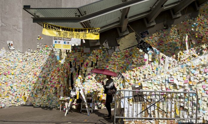 """A woman walks by """"Lennon Wall,"""" which contains messages of support for pro-democracy protesters, in the Occupy Camp in the Admiralty area of Hong Kong on Nov. 17, 2014. (Xaume Olleros/AFP/Getty Images)"""