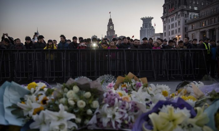 Chinese mourners gather at a makeshift memorial at the site of a stampede on Jan. 1 on the Bund in Shanghai, China. Officials who enjoyed an expensive Japanese meal at a restaurant nearby are coming under scrutiny. (Kevin Frayer/Getty Images)