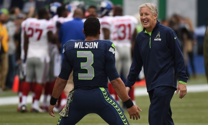 Pete Carroll chats with Russell Wilson as he warms up before the game against the New York Giants at CenturyLink Field on Nov. 9, 2014 in Seattle. (Steve Dykes/Getty Images)