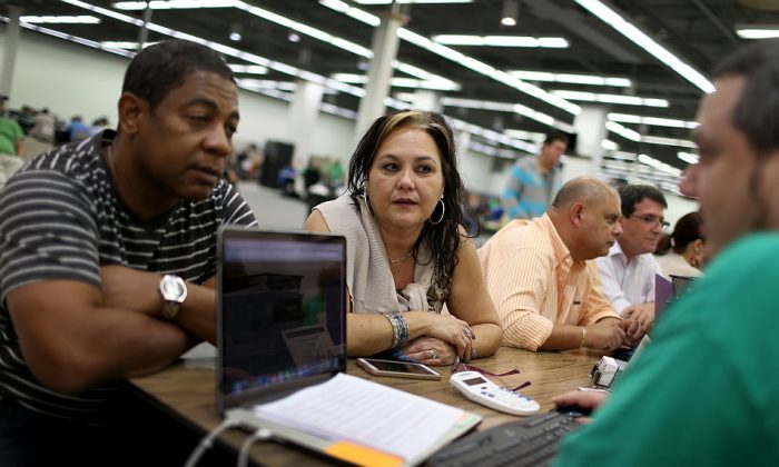 Jose Ramirez and Mariana Silva speak with an agent from Sunshine Life and Health Advisors, as they discuss plans available from the Affordable Care Act in Miami, Florida, on Dec. 15, 2014. (Joe Raedle/Getty Images)