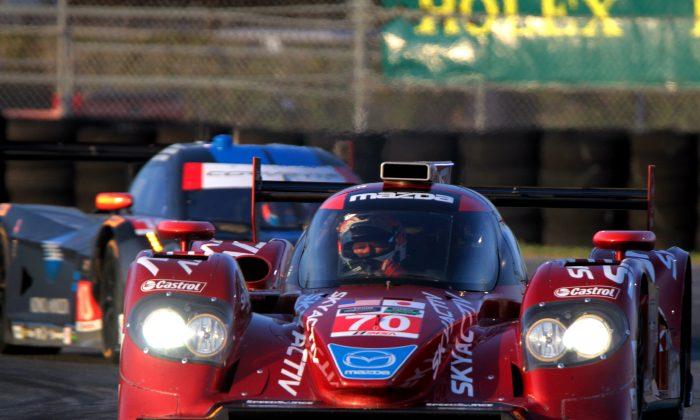 SpeedSource owner/driver Sylvain Tremblay in the #70 Mazda diesel leads the #10 WTR Dallara-Corvette around a corner at Daytona, Jan. 10, 2015. (Chris Jasurek/Epoch Times)