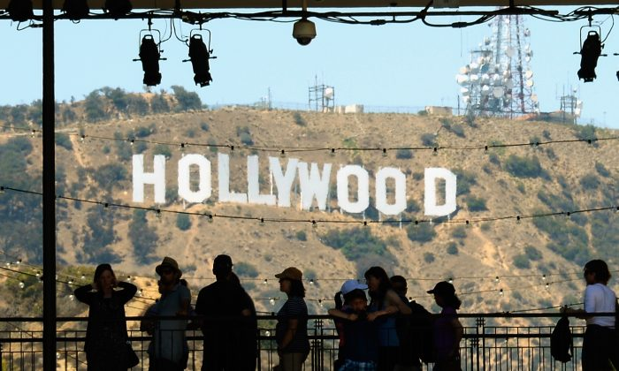 Tourists are silhouetted against the distorted Hollywood sign on June 28, 2013 in Los Angeles, California. The Motion Picture Association of America is suing China's Xunlei for violating an anti-piracy deal. (Kevork Djansezian/Getty Images)