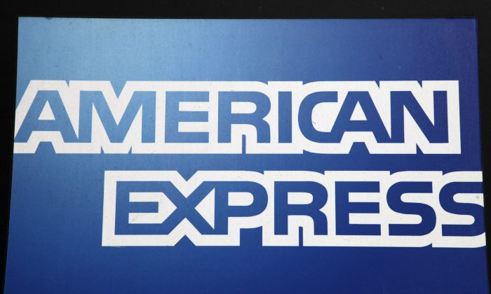 A sign for American Express hangs outside a New York business, Wednesday, Jan. 21, 2015. American Express reports quarterly financial results after the market closes on Wednesday. (AP Photo/Mark Lennihan)